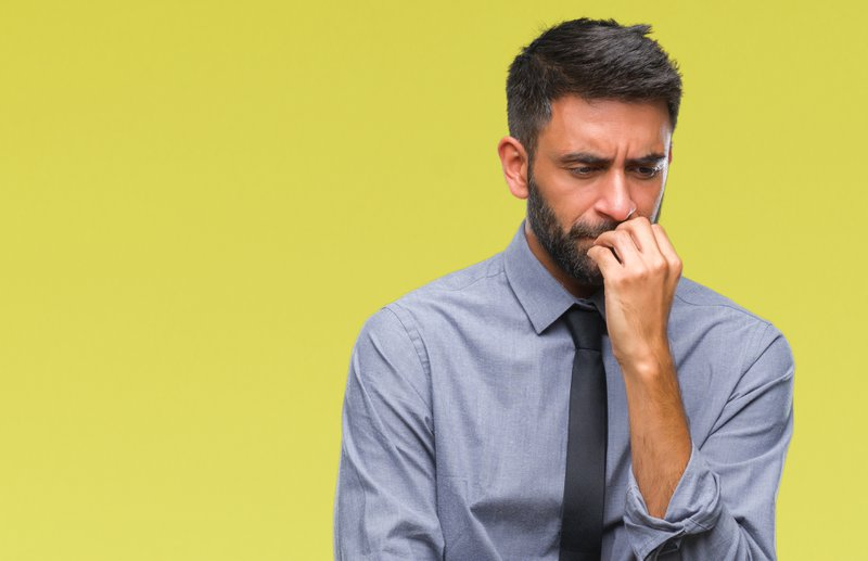 Adult man looking stressed and nervous with hands on mouth biting nails. Anxiety problem owing to stress.