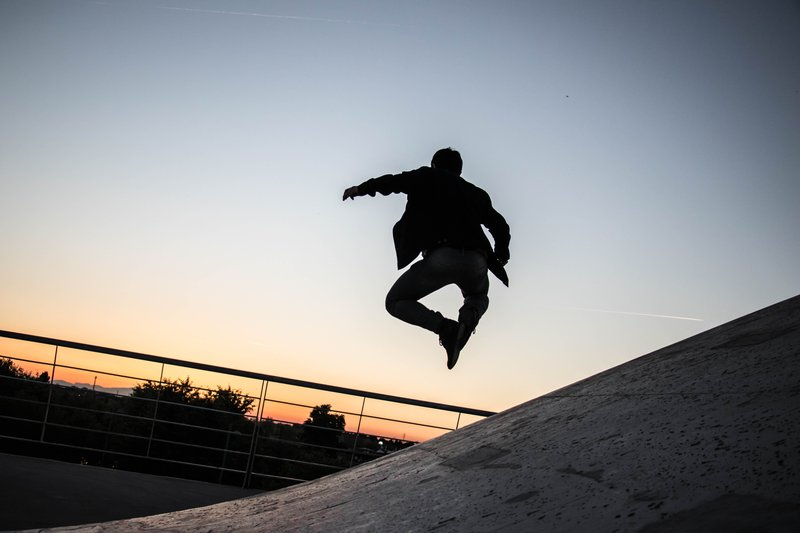 A person jumping high against a sunset in the background.