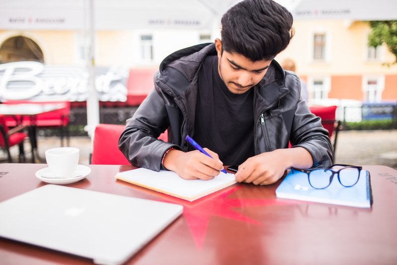 Young man journaling in copybook, noting goals, achievements and failures in time management check list during coffee break at cafe table
