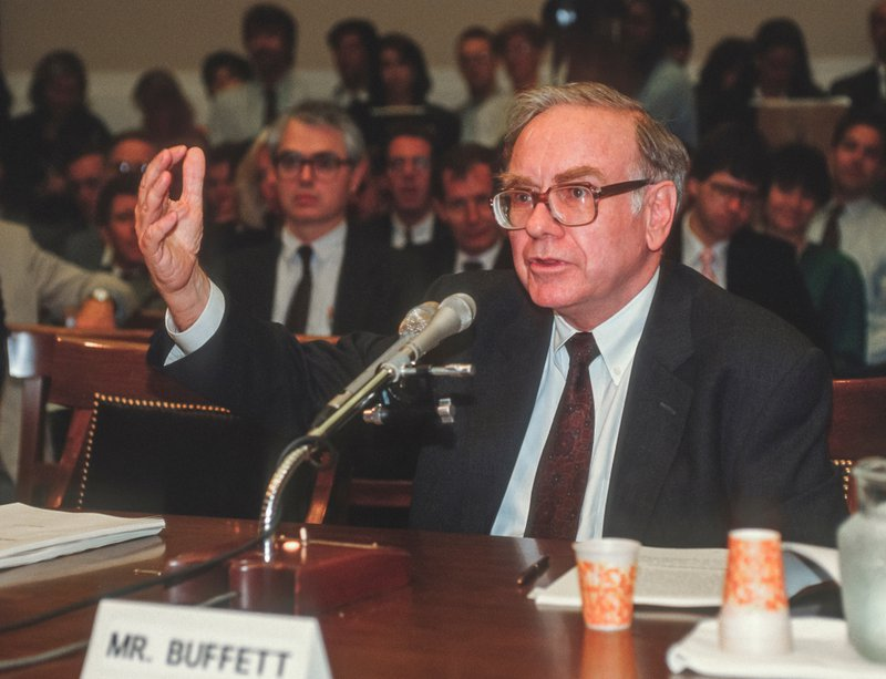 Photograph of Warren Buffet sitting at a table with a crowd behind him. He is speaking on the microphone and has his hand raised in mid-air explaining a point.
