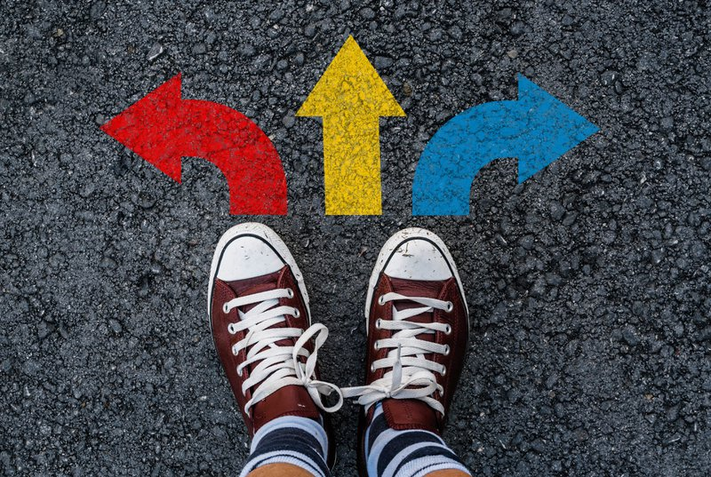 Person wearing shoes standing next to three direction colorful arrow choices, left, right or straight. This indicates the possible different career directions one can choose to go in.