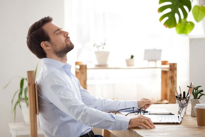 A young man at his desk engaging in a quick mindfulness meditation break