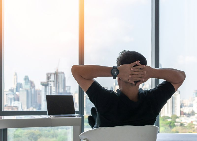 Man stretching in his office with his hands at the back of his head, looking out of the window. Indicating the importance of mental health.