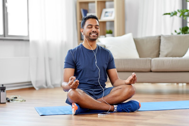 fitness, meditation and healthy lifestyle concept - indian man in earphones listening to music on smartphone and meditating in lotus pose at home helps reduce stress