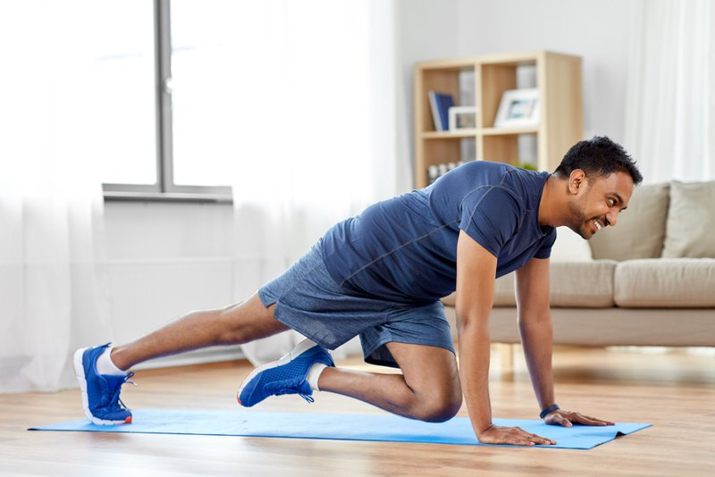 Young man doing running plank exercise at home can help mental health