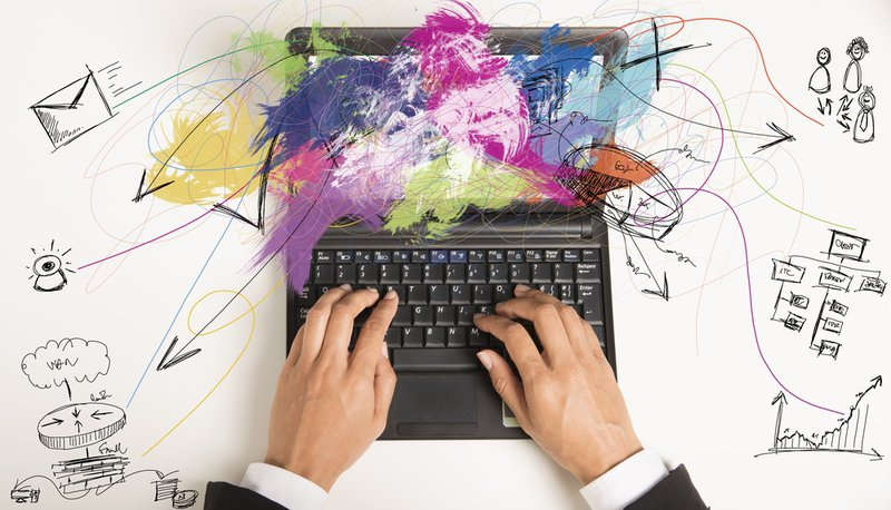 Image to indicate lateral thinking and creativity while a man's hands type on a keyboard and colour and drawings jump out of the screen.