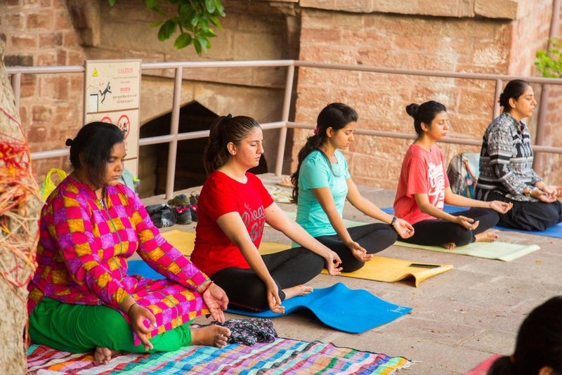 A group of multiethnic women meditation together on yoga mats.