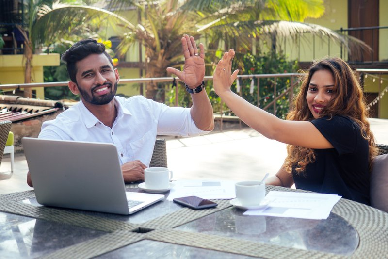 A young man and woman sitting outdoors high-fiving one another as they look at the camera. There is a laptop in front of the man and some paper in front of the woman. A mobile phone and two cups of coffee are on the table as well. Being prepared for career mobility can be a game-changer for individuals.