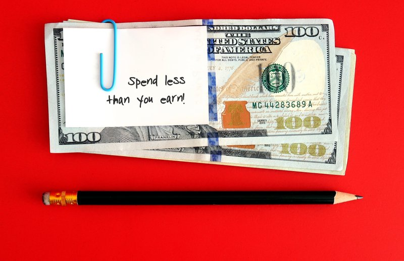 a bundle of dollars with a note that says 'spend less than you earn' and a pendil against a red background. The message encourages budgeting.