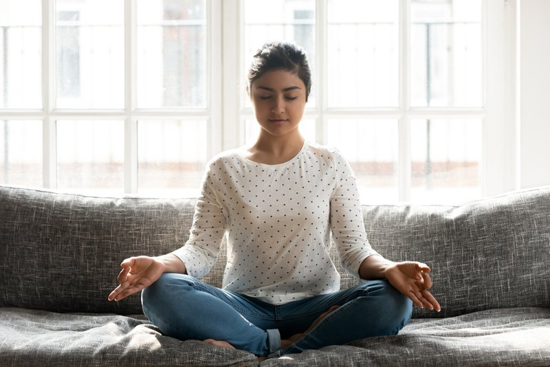 Full length mindful young indian woman making mudra gesture, sitting in lotus position on comfortable couch at home.