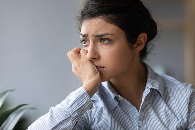 Sad melancholic young indian woman pensive face looking away