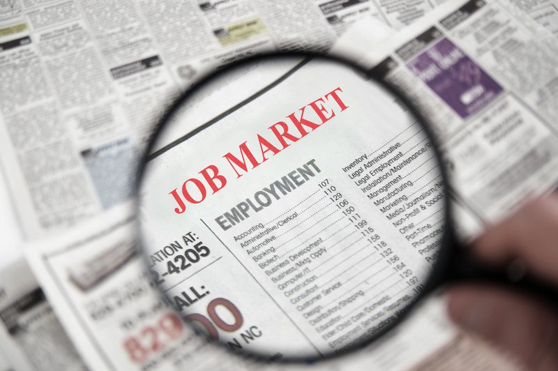 Magnifying glass over a newspaper classified section with Job Market text. The job market at a point in time affects our career options.