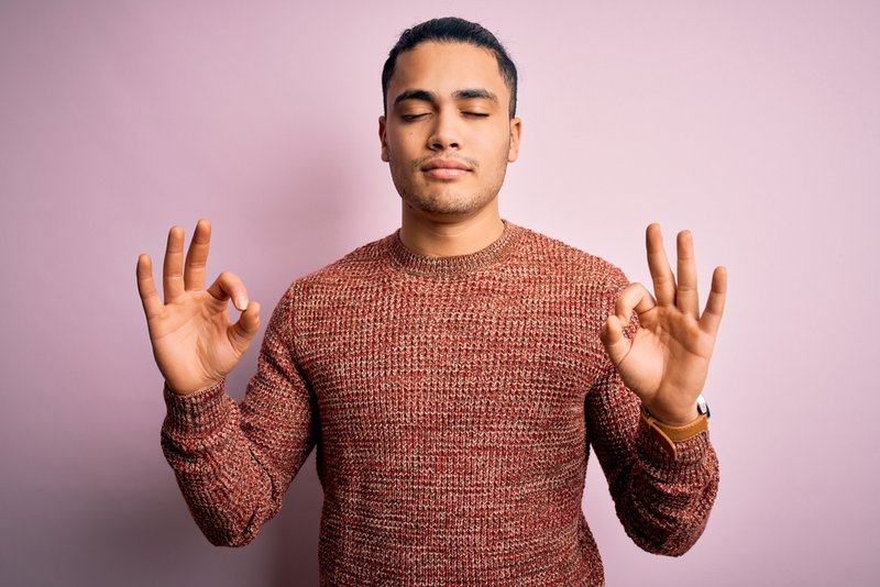Young man wearing casual sweater standing over isolated pink background relax and smiling with eyes closed doing and doing mindful breathing