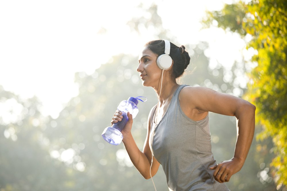 Woman in sportswear listening music during exercise at park outdoor for mental health