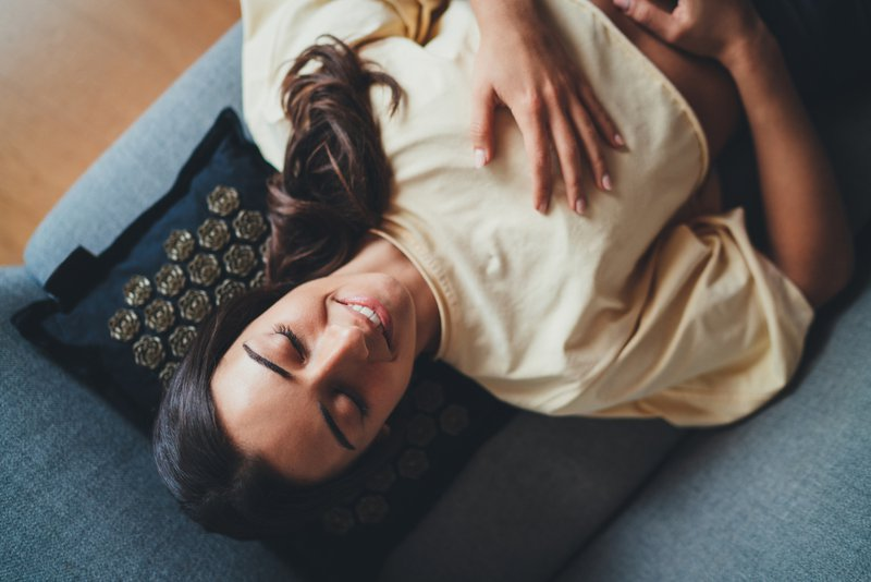 Image of a woman lying with her eyes closed on a pillow and smiling. She is practising mindful breathing.