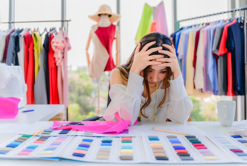 Young asian woman tailor designer failing and stressed from her business startup in workplace office. Stress impacts our creativity.