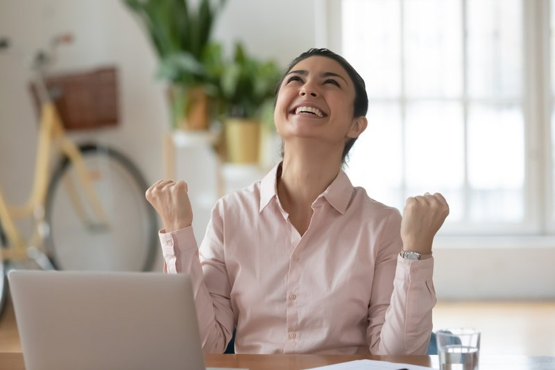 A young woman sitting at a desk in front of her laptop looking up smiling with her fists closed in the air to indicate victory. It indicates growing one's wealth in the younger year's of life.