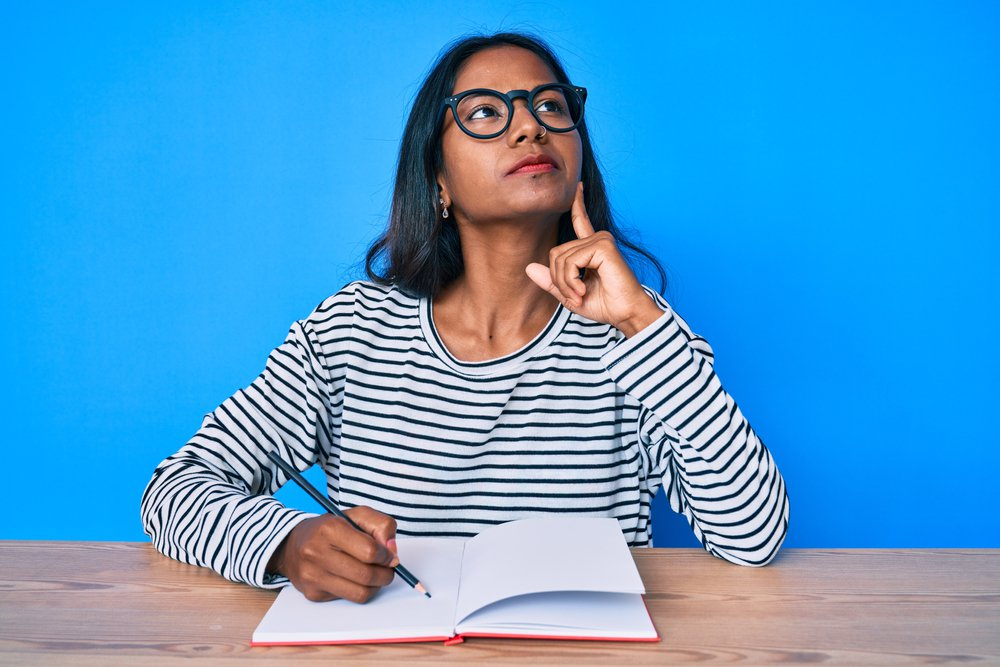 Young indian girl writing notebook sitting on the table serious face thinking about question with hand on chin, thoughtful about what to journal about