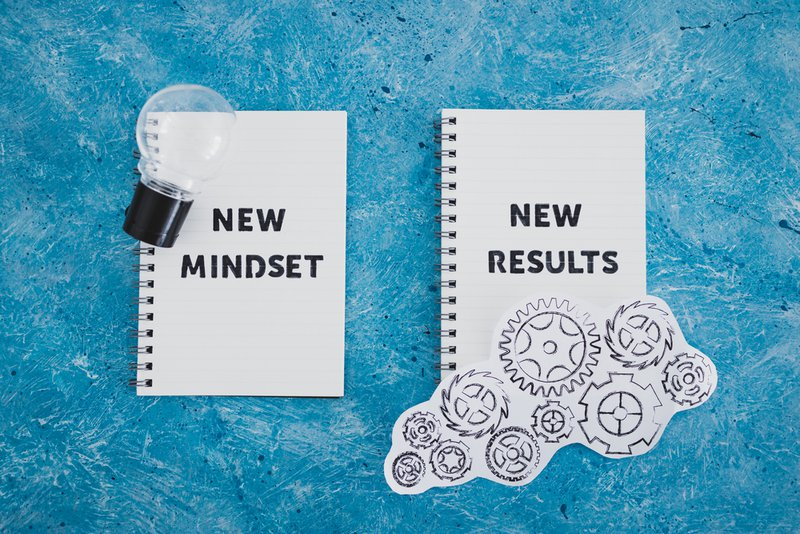 otepad with New Mindset New Results text with light bulb and gearwheel mechanism. The image indicates the mindset shift needed to save better.
