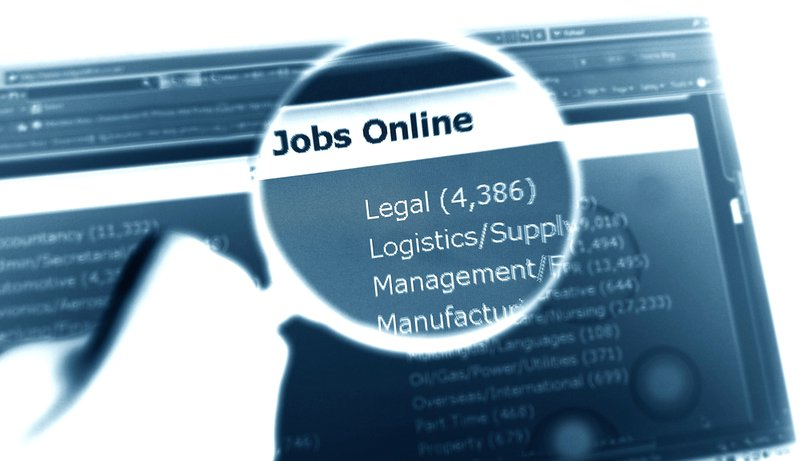 On-line jobs concept with magnifying glass and laptop screen