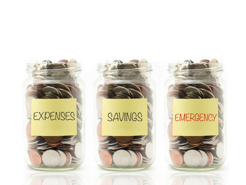 Coins in jar with expenses, savings and emergency label.
