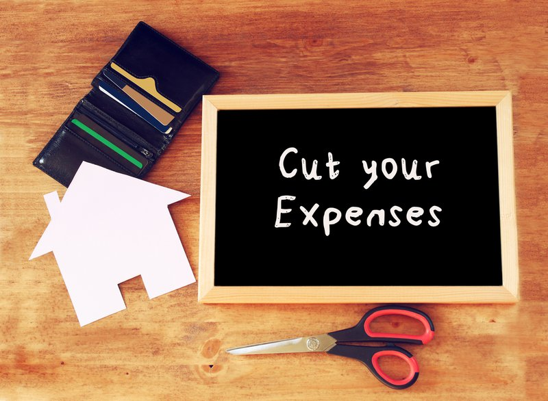 """top view of blackboard with the slogan """"cut your expenses"""" scissors, wallet with credit cards and house shaped paper. Reducing expenses is more or equally effective as earning more."""