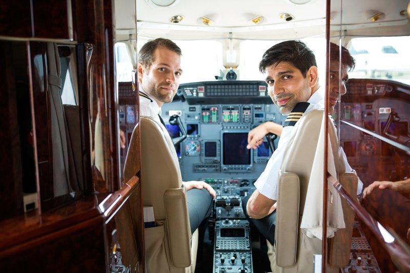 Portrait of confident pilots in corporate plane cockpit.