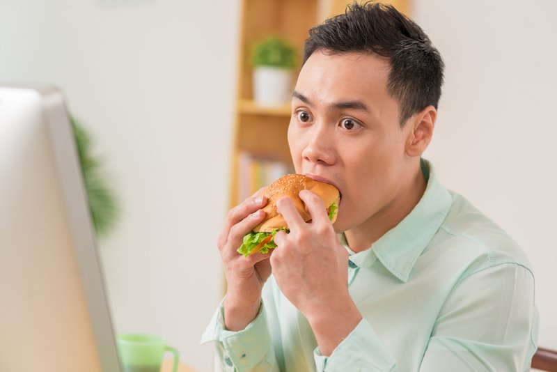 An Asian man looking stressed in front of his computer, stress eating a hamburger.
