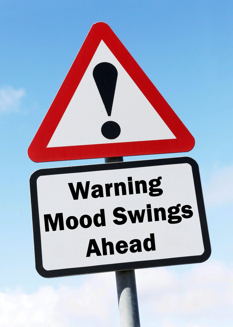 Red and white triangular road sign with warning of a Mood Swings Ahead concept against a partly cloudy sky background