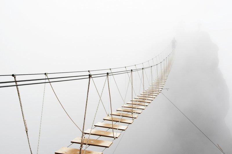 Man walking on hanging bridge vanishing in fog to indicate ambiguity