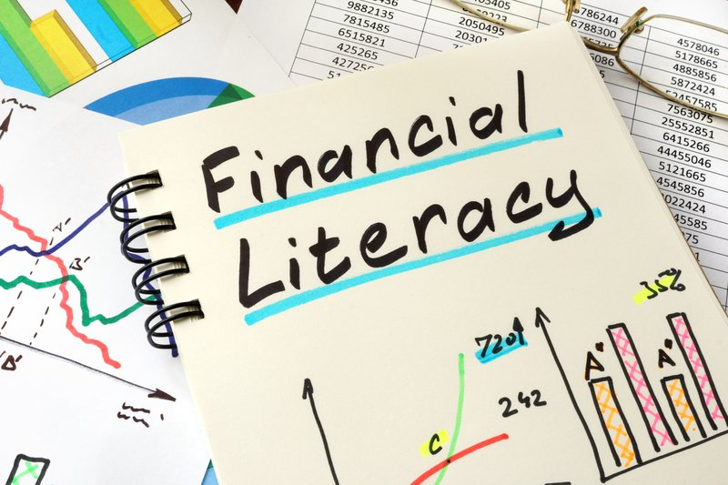Image shows the words 'Financial Literacy' written on a notebook kept on a desk. Financial literacy is a key skill for career mobility.