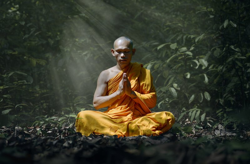 Monk with folded hands, wearing yellow robes meditating with eyes shut.