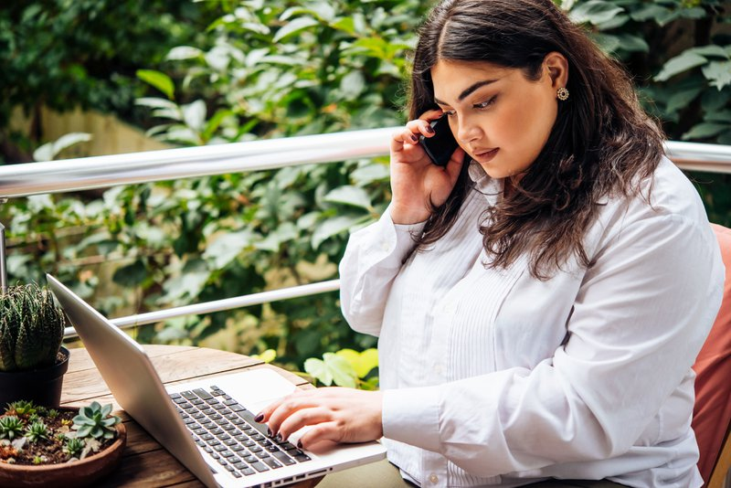 Portrait of a woman working on her laptop on balcony. Choosing a career that gives us energy is the best decision to make.