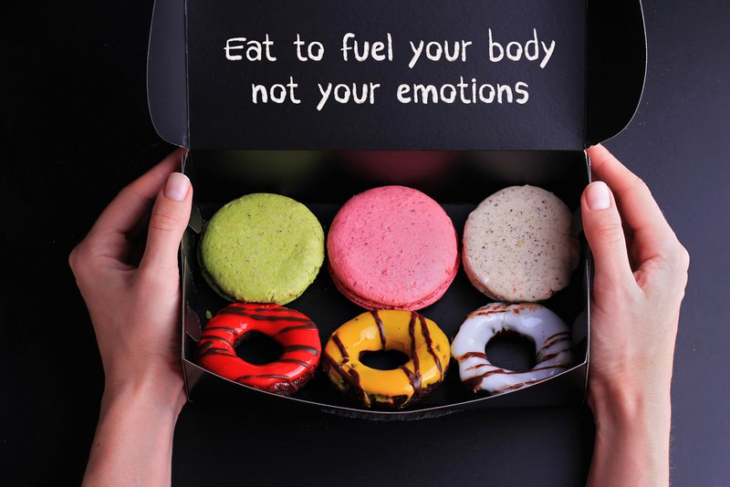 Inspiration motivation quotelet: Eat to fuel your body not your emotions. Diet, Sport, Fitness, Mindfulness, Healthy lifestyle concept. The quote is shown above a box of macarons and doughnuts.