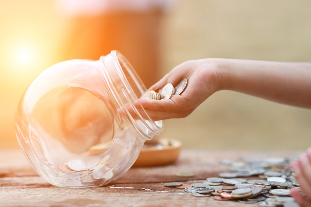 Image of a hand putting coins into a transparent jar to indicate the concept of saving.