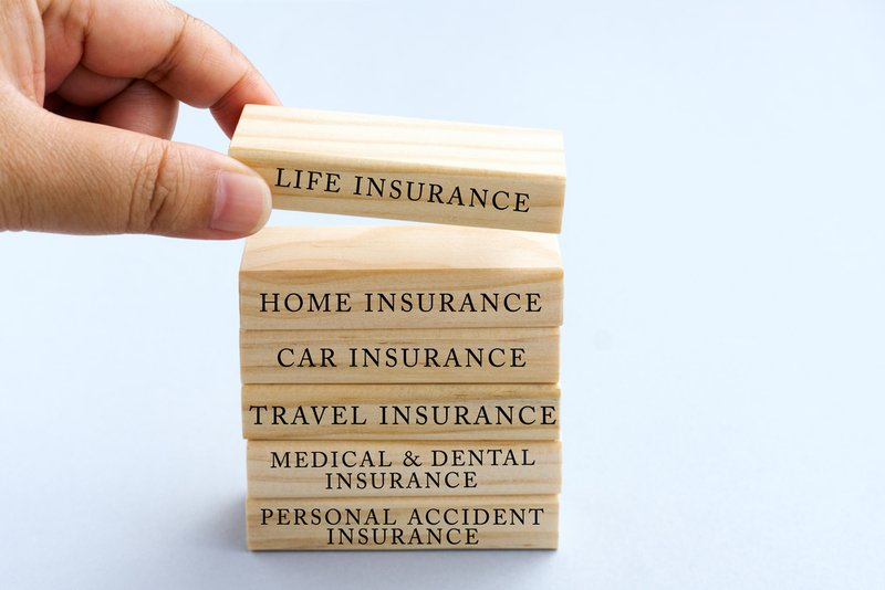 Hand Picking Wood Block with Word Life Insurance. Business Concept Type of Insurances on Wood Top Block with Word: Life, Home, Car, Travel, Medical and Dental, Personal Accident.