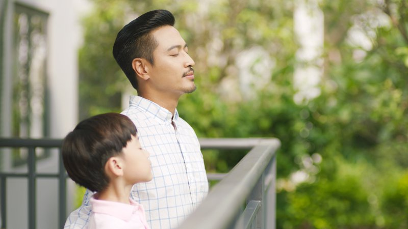 father and his son standing on balcony enjoying deep breathing which is a great technique to battle stress and practise mindfulness