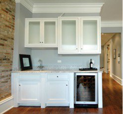 A home bar with white cabinet and glass panel wall cabinets.