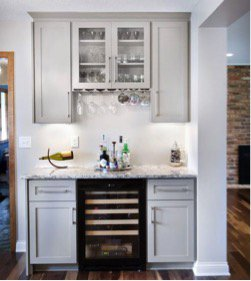 A small, bright home bar with a wine cooler.