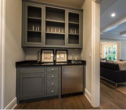 A small, built-in home bar with a min-fridge.