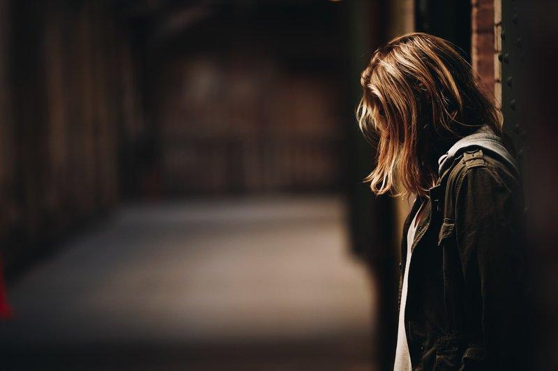 A girl stands in a dimly lit hallway on Alcatraz Island, SF.