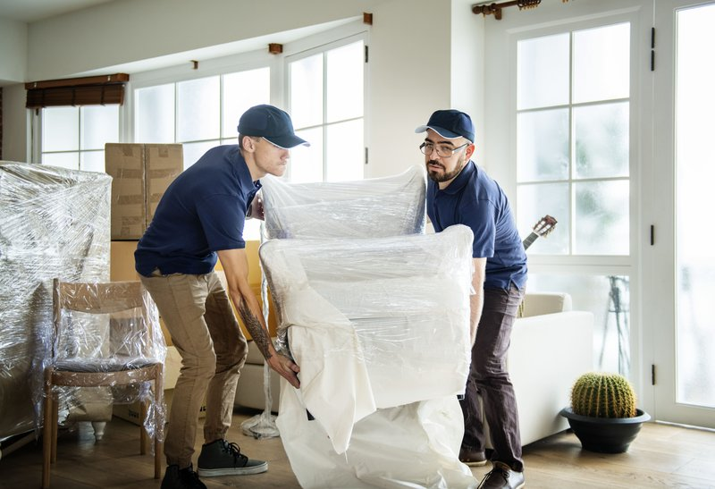 Packers and movers carrying furniture