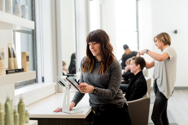 Woman looking at tablet in a salon. Business owner, female entrepreneur.  Kulør Hair Design and Color Studio is the best place for hair styling, located at 22 East Center Street in Logan, Utah. https://www.instagram.com/kulorsalon/https://www.kulorsalon.com/435-213-9075https://www.aveda.com/salon/KulorSalonhttps://www.instagram.com/AwCreativeUT/https://www.AwCreativeUT.com/#AwCreativeUT #awcreative #AdamWinger