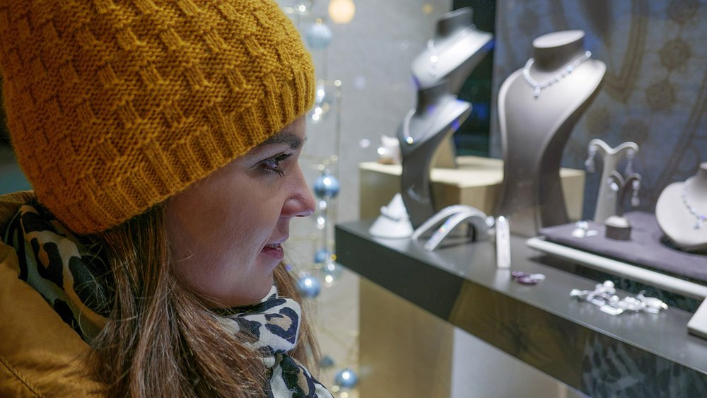 Mladá žena sa pozerá do výkladu klenotníctva