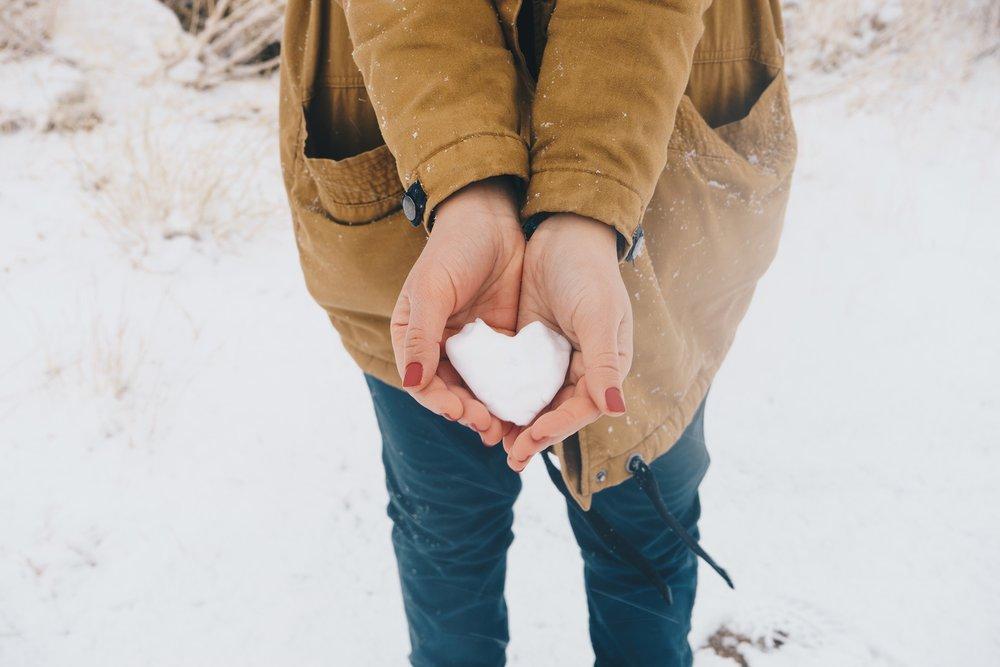 Žena drží v rukách sneh v tvare srdca