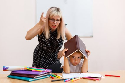 the teacher screams at the little schoolgirl. little girl with a closed book sitting at a desk in the classroom
