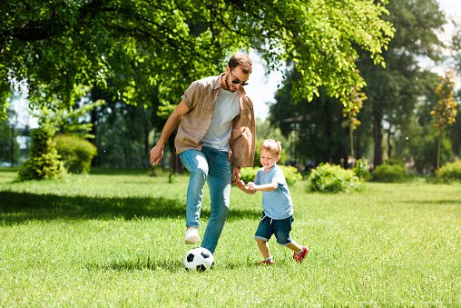 dad and son playing football at park