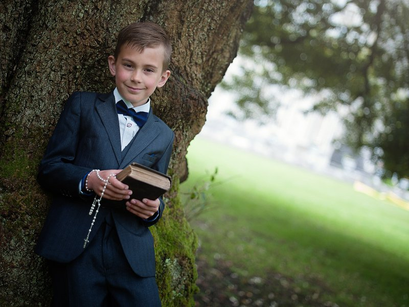 Boy in navy suit posing for a family portrait in Johnstown Castle Wexford