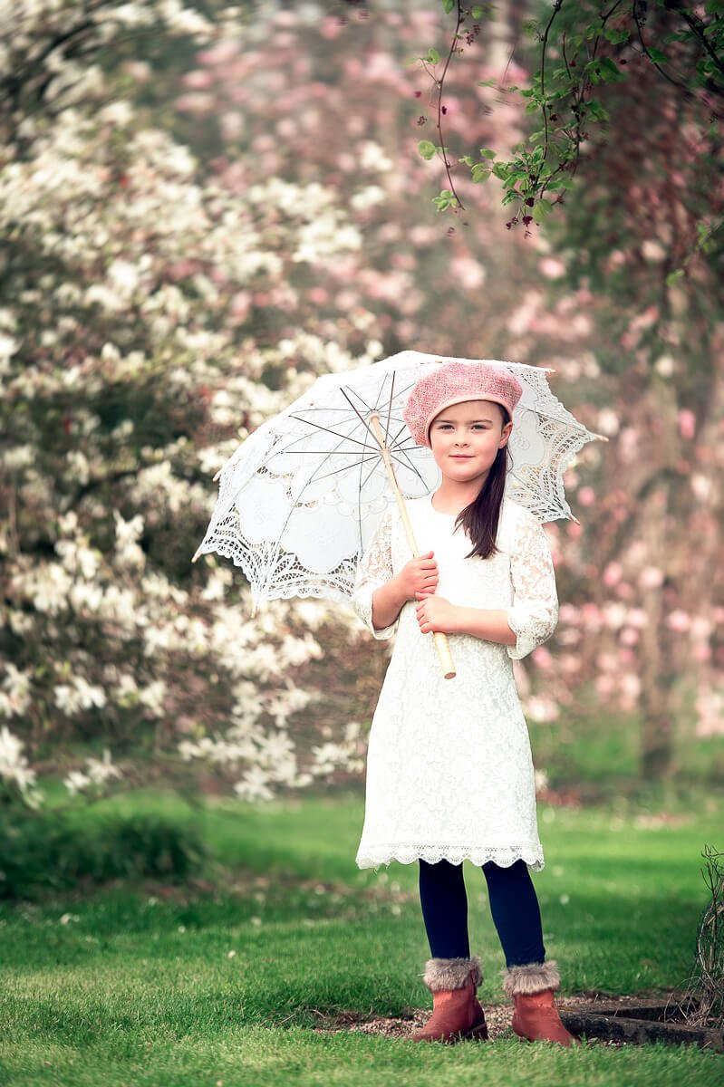 Girl in white dress with umbrella on a family portraits in Kennedy Park Wexford