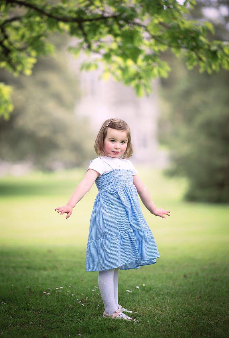 Little girl in blue dress on family photo session in Johnstown castle,Wexford